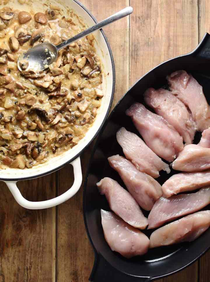 Top down view of raw chicken pieces in black oval dish and mushroom sauce with spoon in white round dish.