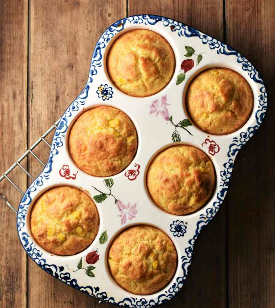 6 cornmeal muffins in ceramic pan with blue flowery pattern on top of rack.