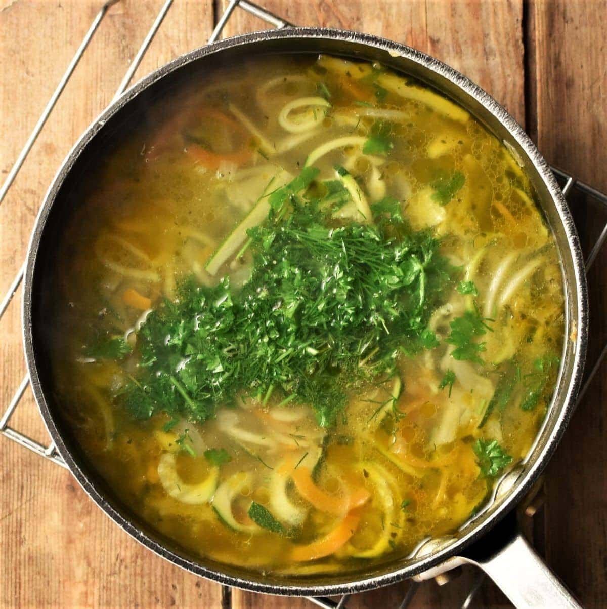 Spiralised vegetable soup with herbs in pot.