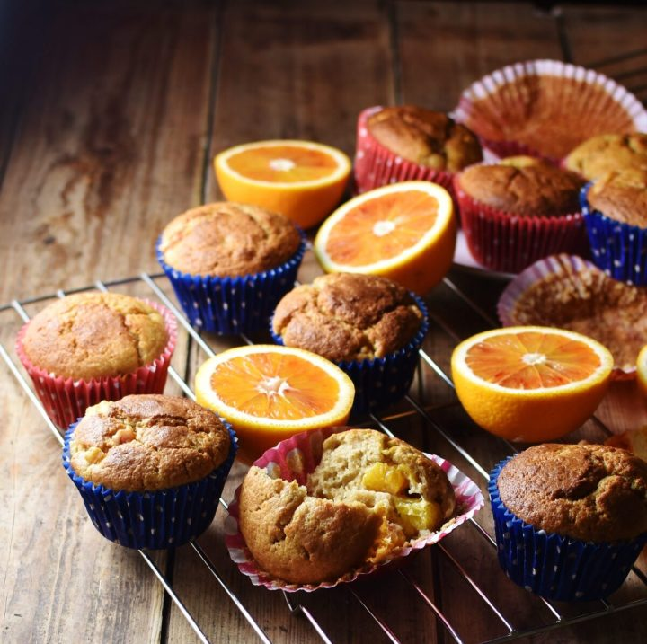 Side view of muffins in blue and red paper cases and halved blood oranges on top of cooling rack.