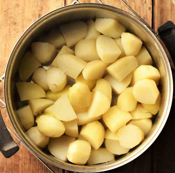 Cubed peeled potatoes in pot.