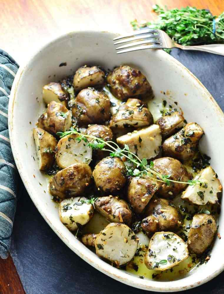 Roasted Jerusalem artichoke halves with lemon thyme in white oval dish with fork and fresh herbs in top right corner on dark grey surface.
