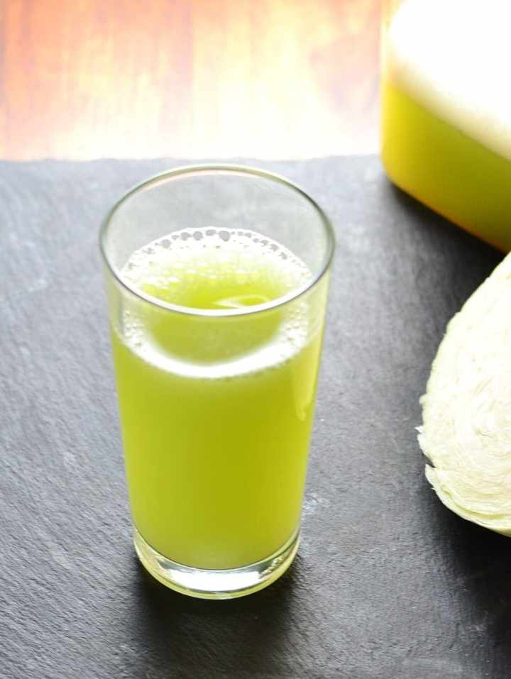 Cabbage juice in glass with melon and cucumber on slate surface.