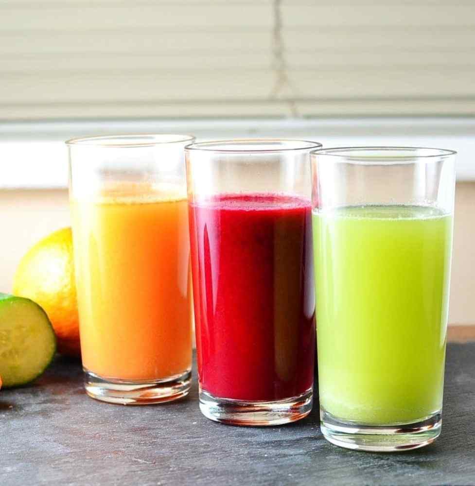 Cabbage juice in 3 glasses, green, red and orange, with fruit and vegetable in background on slate surface.