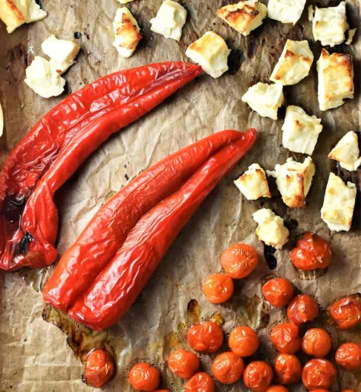 Roasted sweet red peppers, cherry tomatoes and chunks of feta on top of parchment.
