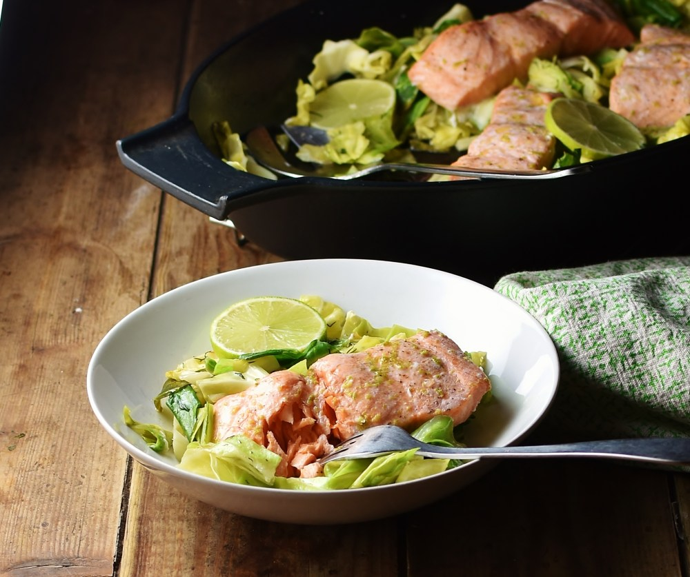 Side view of salmon and cabbage in white bowl with fork, green cloth and black dish with salmon and cabbage in background.