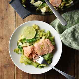 Salmon with chopped cabbage and fork in white bowl, with green cloth and black dish with salmon in background.