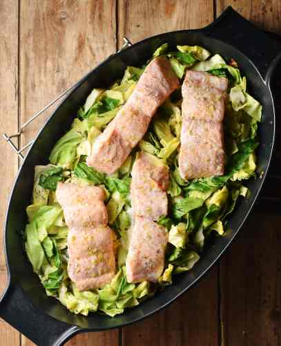 4 salmon pieces on a bed of cabbage in black oval dish.