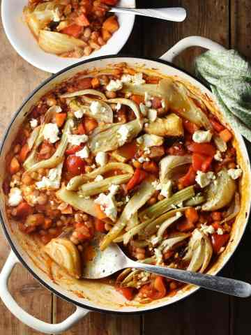 Top down view of bean, vegetable and fennel casserole with pieces of feta in large shallow white dish with spoon, green cloth in top right and casserole in small bowl at the top.