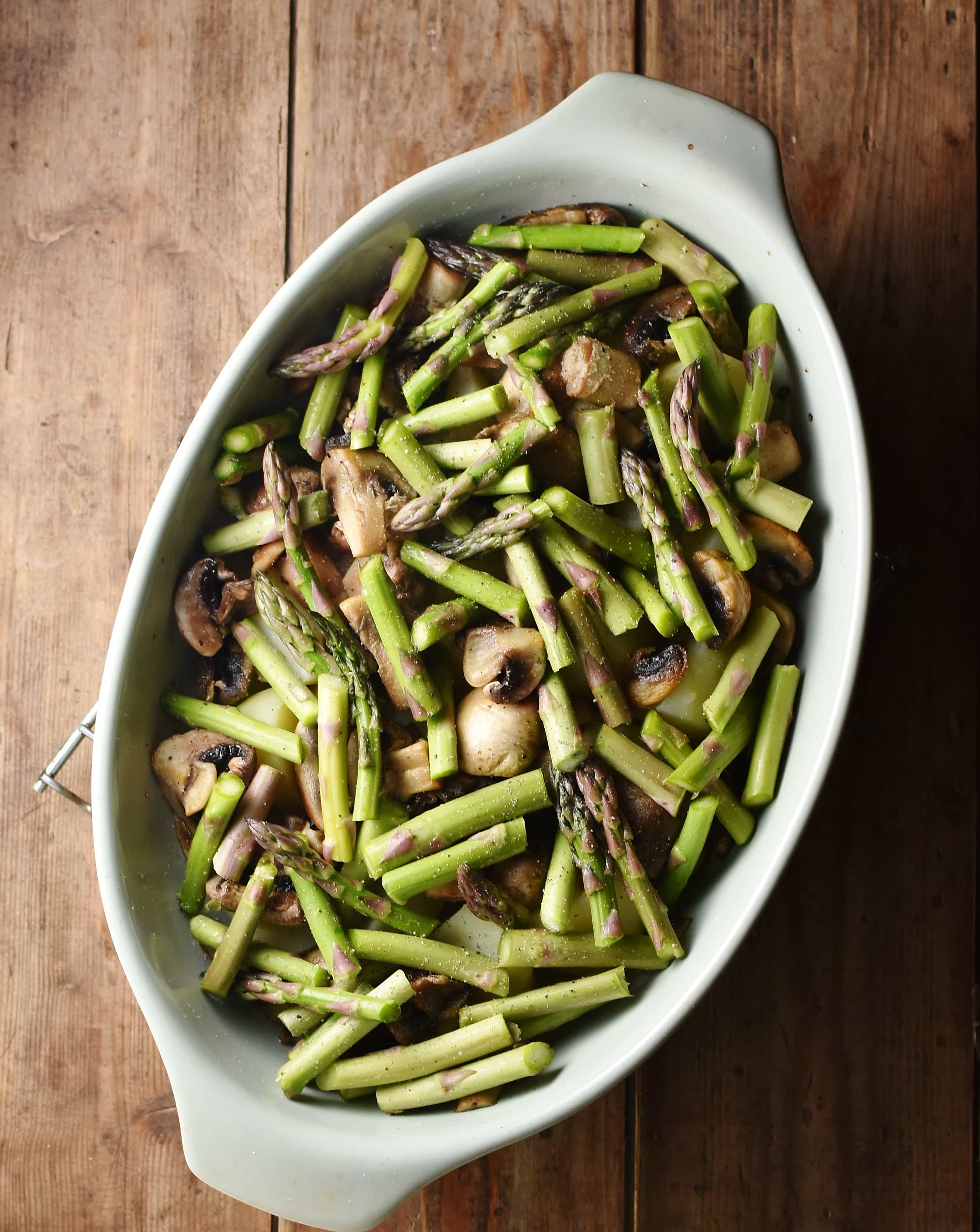 Chopped asparagus and mushrooms in oval dish.