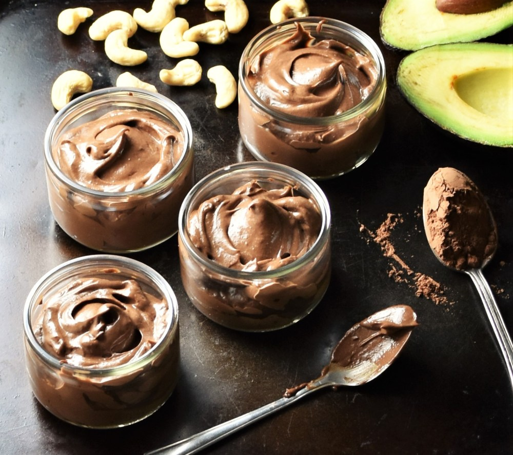Healthy chocolate avocado mousse in 4 round pots, 2 spoons with cocoa, cashew and halved avocado.