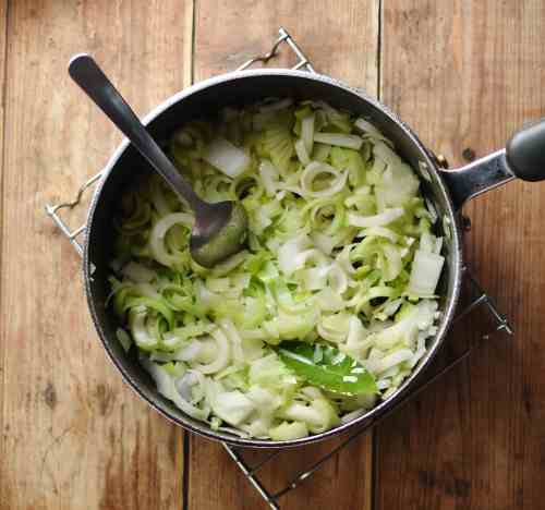 Chopped vegetables with spoon inside large pot.