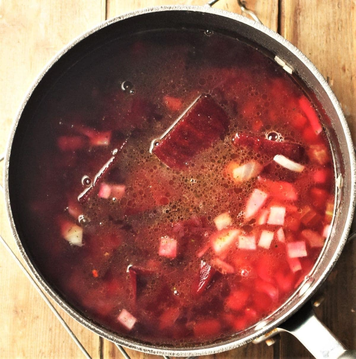 Making vegan borscht in pot with beetroot pieces visible.