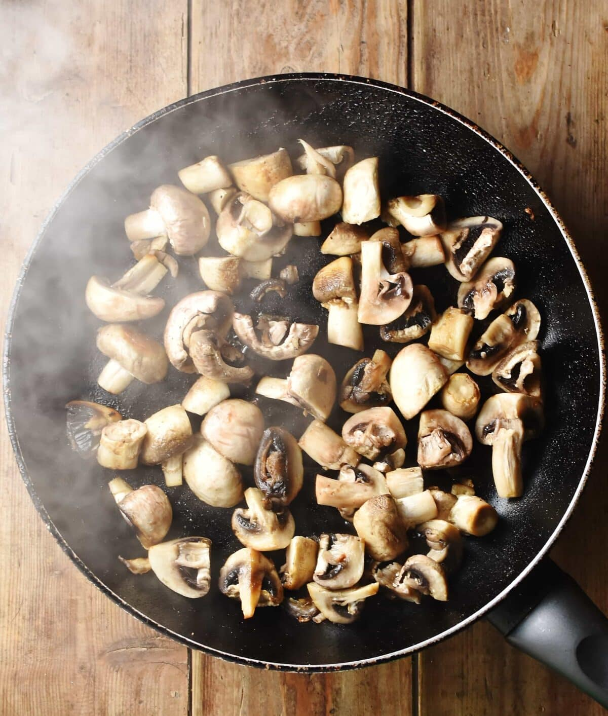 Chopped mushrooms in large pan with steam visible.