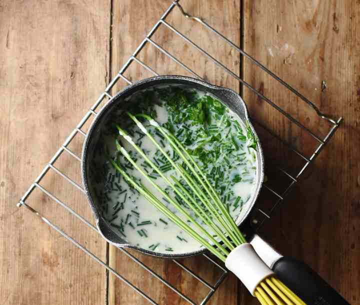 Sauce with herbs and green whisk in saucepan.