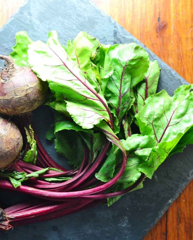 Beet greens with beetroot on square slate surface.