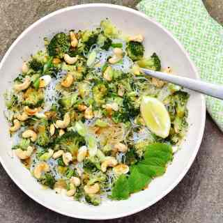 Top down view of bean thread noodles broccoli salad with cashews, lemon wedge, mint leaves and fork in white bowl with green cloth to right.