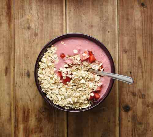 Top down view of strawberry mixture, oats and chopped strawberries with spoon in purple bowl.