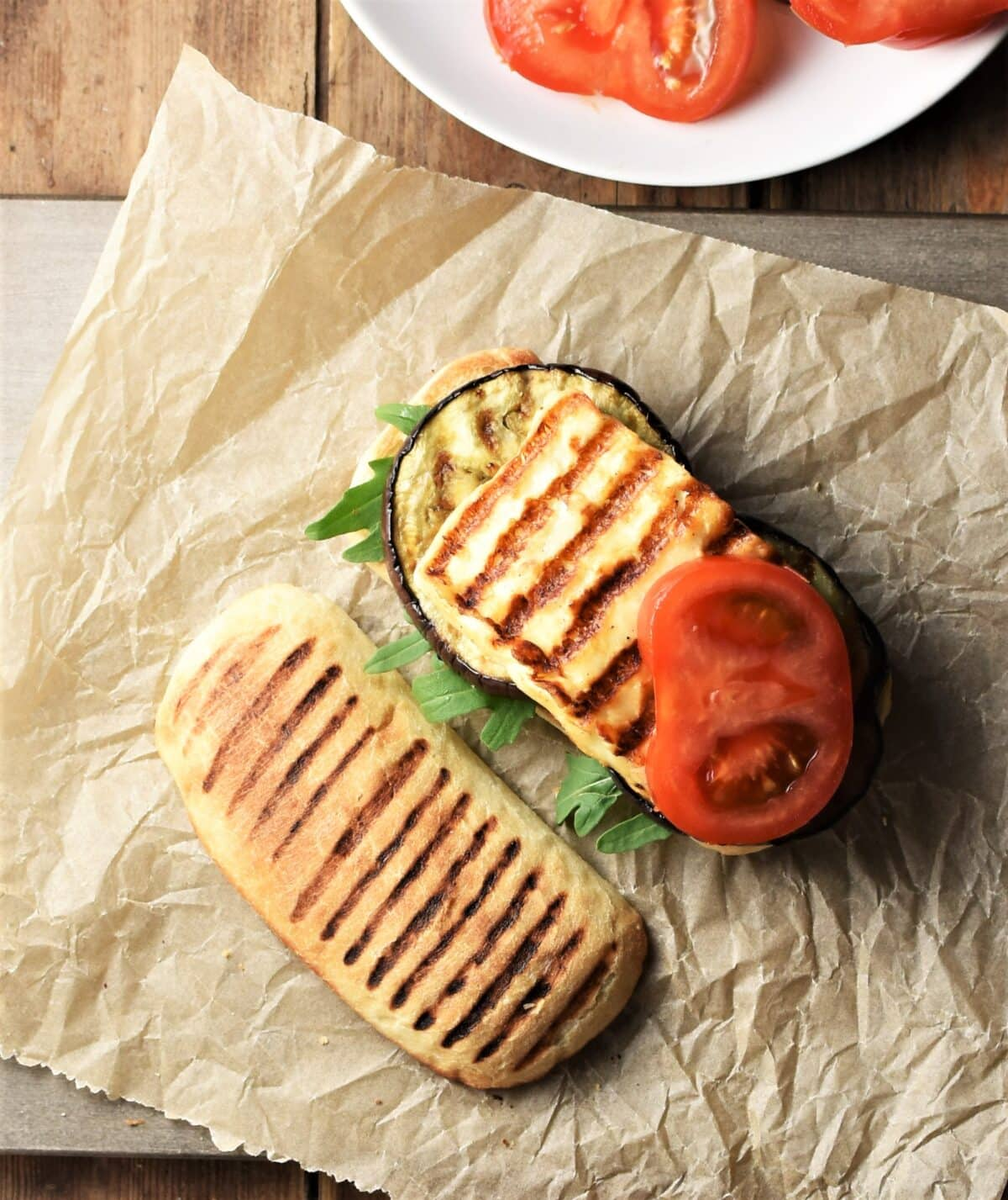 Top down view of open grilled eggplant and halloumi sandwich with tomato on top of paper.