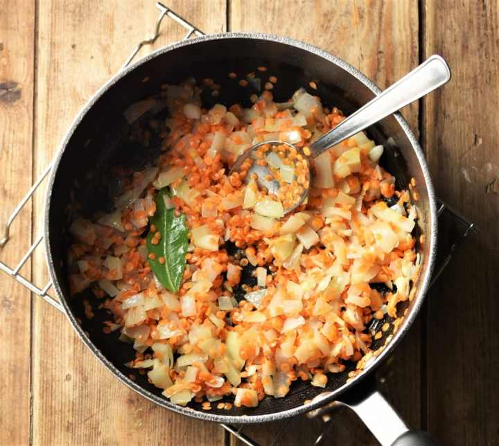 Red lentils, chopped onion and bay leaf in large pot with spoon.
