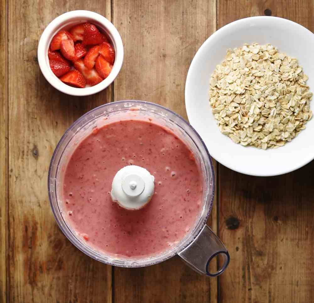 Top down view of pureed strawberry mixture in blender with oats in white bowl and strawberries in white dish.