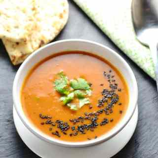 Creamy red vegetable soup with garnish of black sesame seeds and cilantro in white bowl on white plate, with pita bread and spoon on top of green cloth in background.