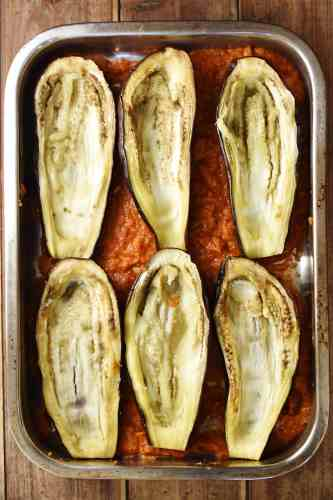 6 eggplant halves in tomato sauce in large oven dish.