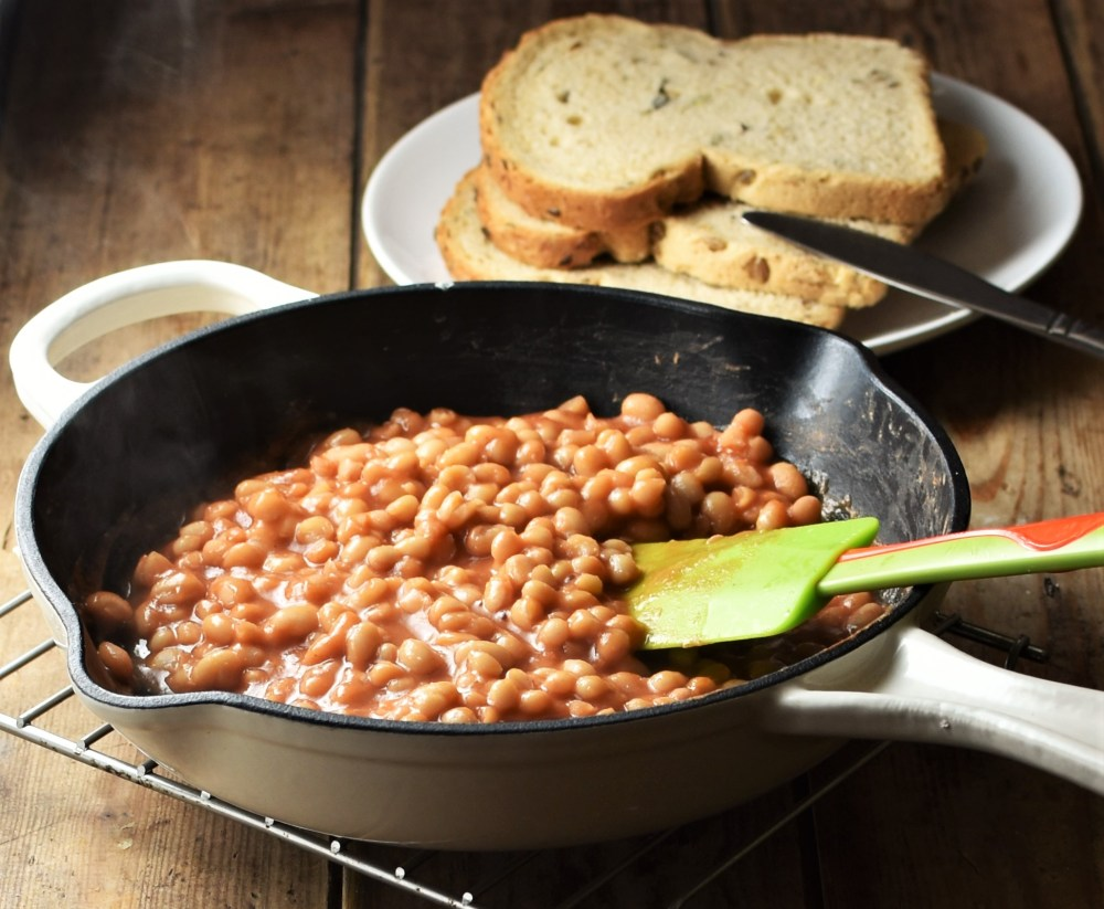 Side view of baked beans in skillet with green spatula and slices of bread in background.