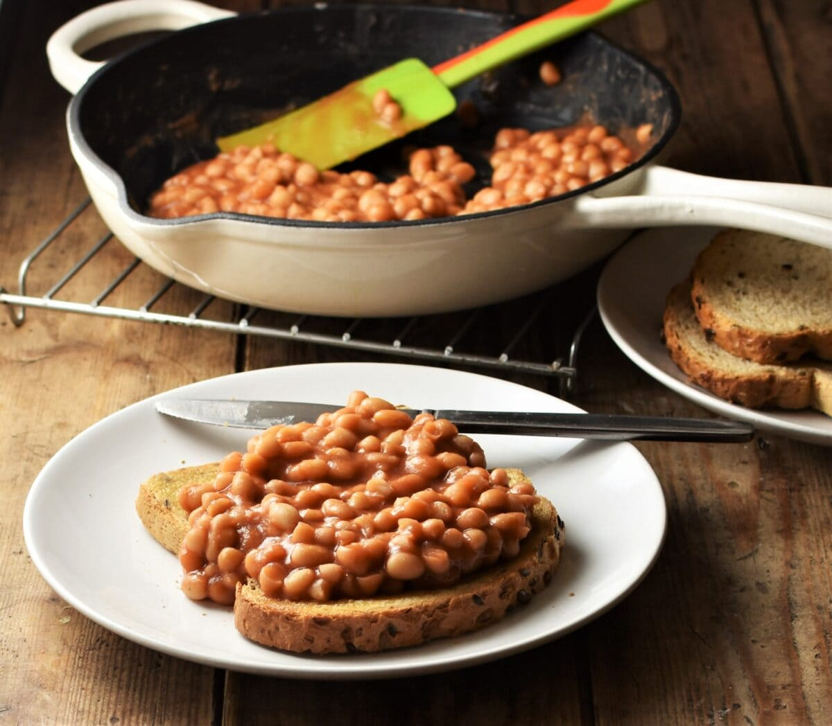 Side view of toast with baked beans and knife on white plate with beans in skillet in background.