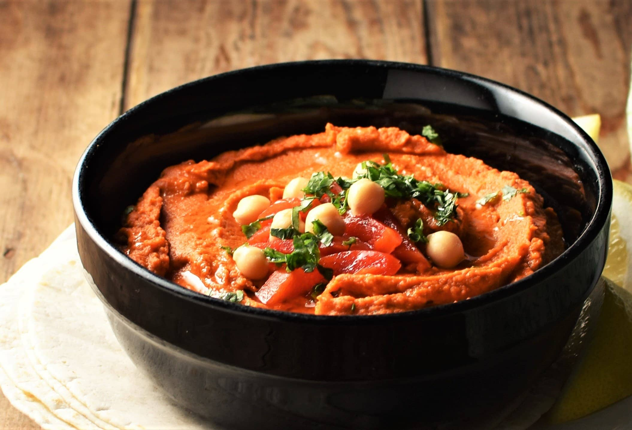 Side view of creamy red pepper hummus in black bowl.