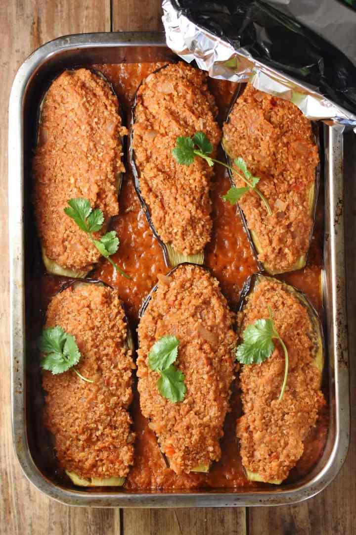 6 quinoa stuffed eggplant halves in tomato sauce in large rectangle oven dish with cilantro leaves on top.