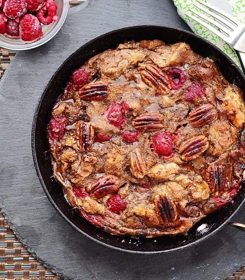Top down close-up view of raspberry french toast with pecans in skillet.