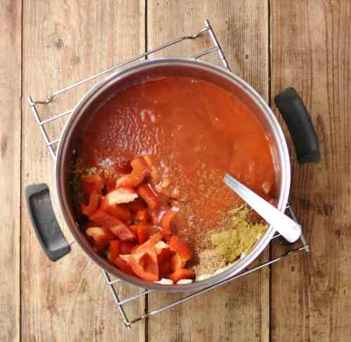 Chopped pepper, tomato puree, spices and spoon in saucepan.