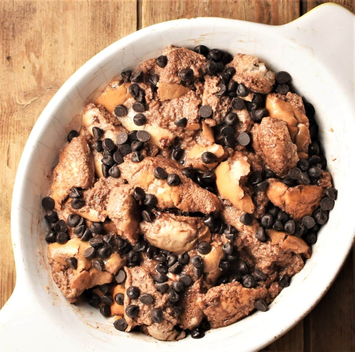 Making chocolate french toast casserole with chocolate chips in oval dish.