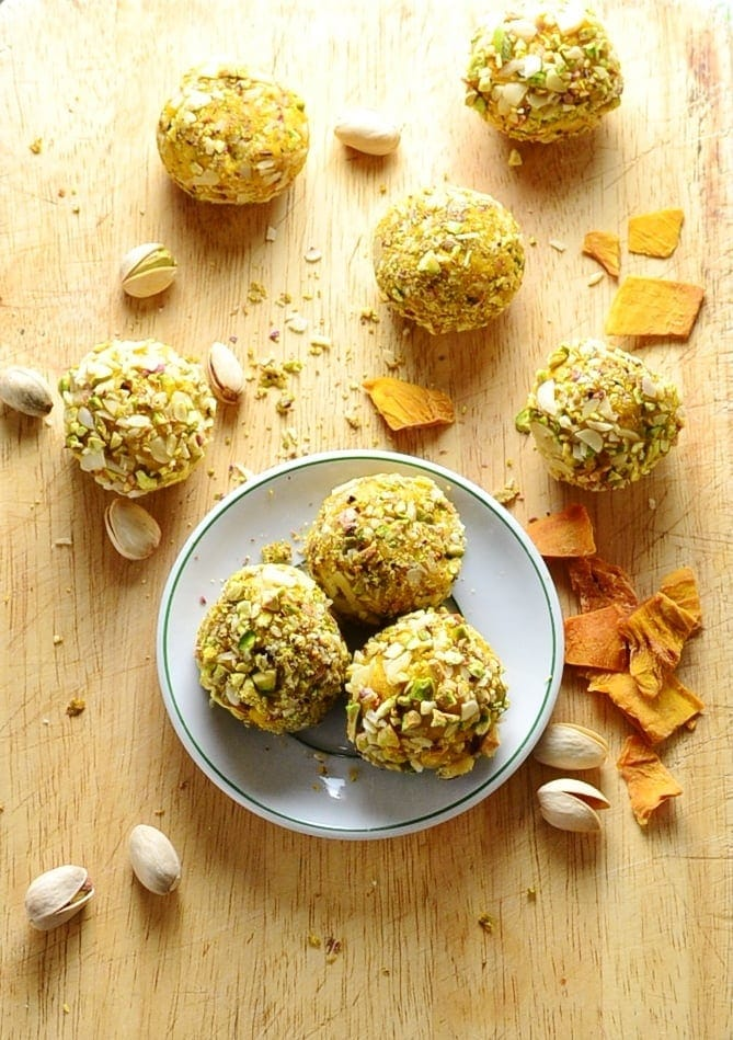 Top down view of mango cheesecake balls on small white plate on top of wooden surface, with dried mango pieces and pistachio scattered around.
