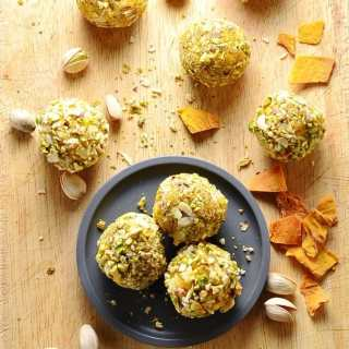 Top down view of mango cheesecake bites on small grey plate on top of wooden surface, with dried mango pieces and pistachios.