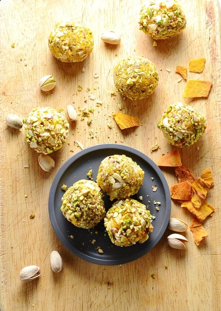 Top down view of mango cheesecake bites on small grey plate and wooden surface with dried mango pieces and pistachios.