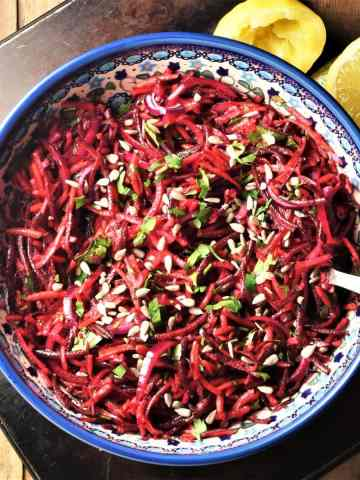 Shredded raw beet salad in large blue bowl with lemon in background.
