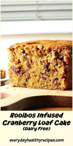 Close-up side view of cranberry loaf cake on top of wooden board.