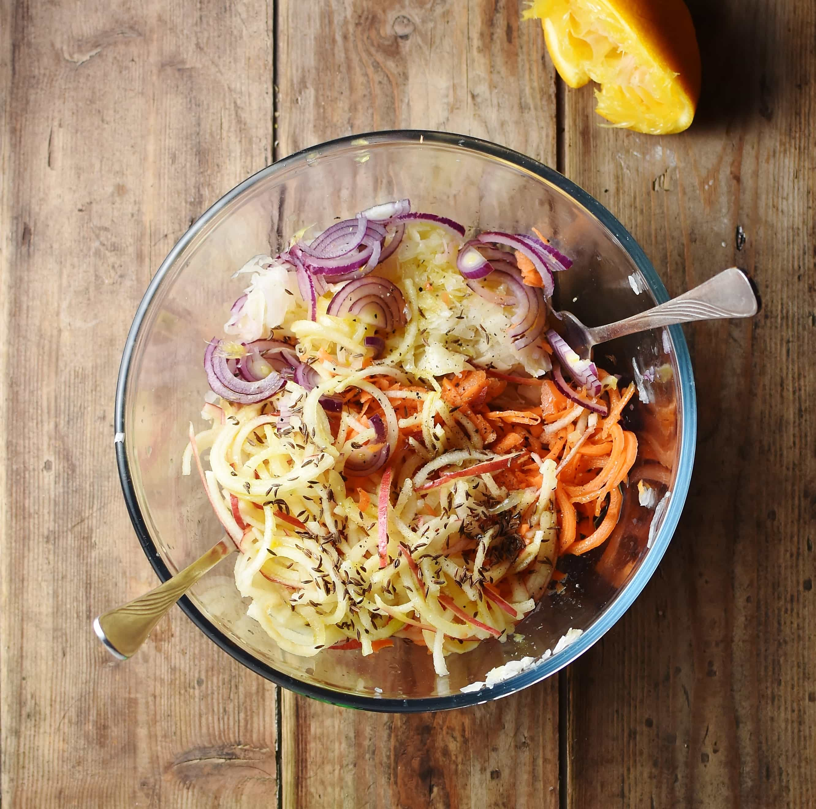 Spiralized carrot and apple, sliced red onion, spices and sauerkraut in mixing bowl with 2 forks.
