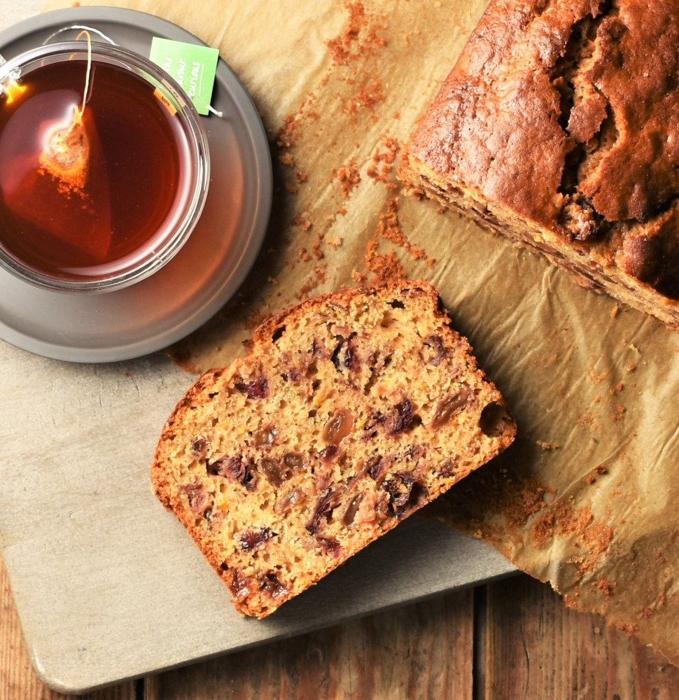 Slice of tea loaf cake, rooibos tea and partial view of tea cake on top of parchment.