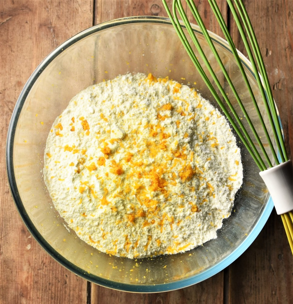 Flour mixture and orange zest in mixing bowl with green whisk on top.