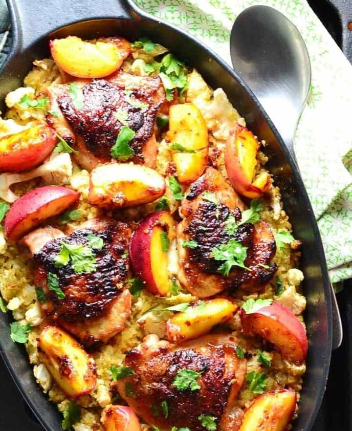 Top down partial view of crispy chicken with peaches on a bed of cauliflower and bulgur inside black oval casserole dish, with spoon on top of green cloth to the right.