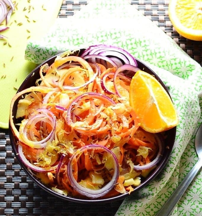 Sauerkraut salad in purple bowl with orange, green cloth and partial view of yellow board.