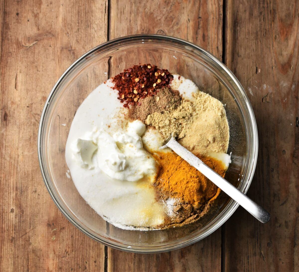 Yogurt and spices in mixing bowl with spoon.