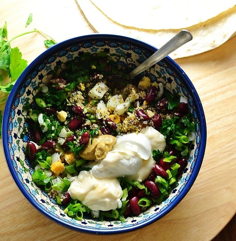 Top down view of mixture of egg, beans, onions, mustard, quinoa and yogurt in blue bowl with spoon on top of wooden surface with wraps at top