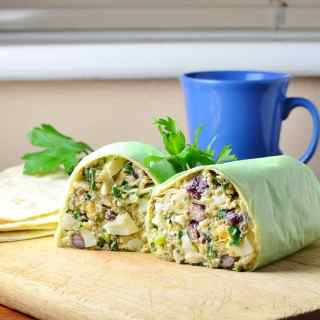 Side view of halved egg salad wrap on top of wooden board with parsley leaves and blue cup in background.