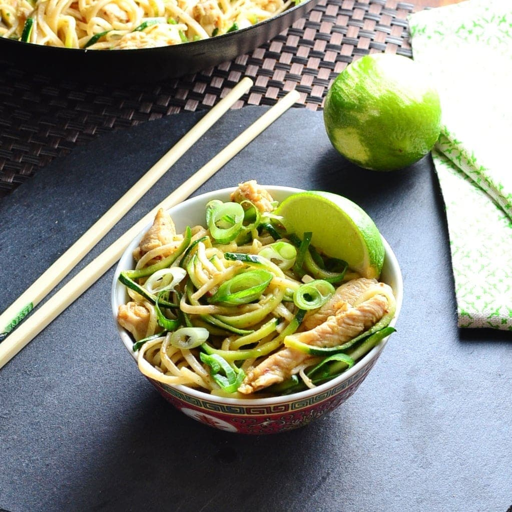 Hoisin chicken stir fry with lime, chopsticks and green cloth on black surface.