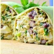 Side view of halved egg salad wrap on top of wooden board with parsley leaves in background.