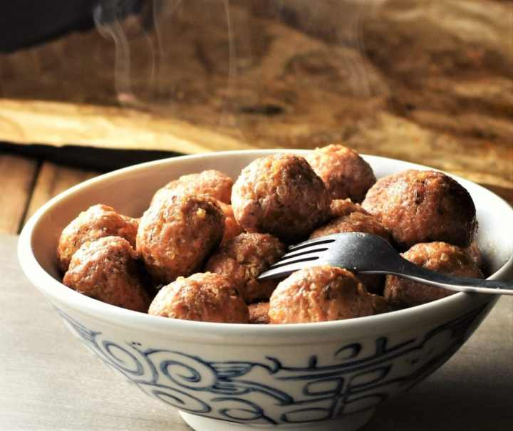 Side view of meatballs in bowl with fork.